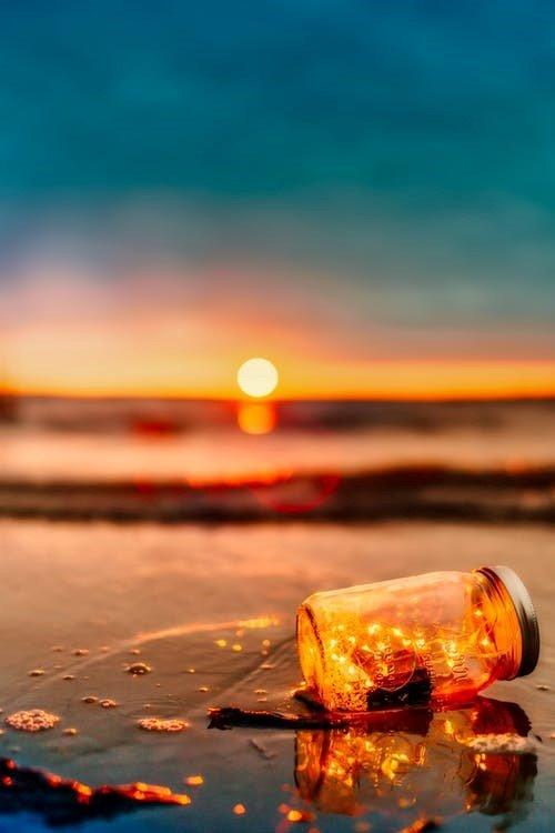 Foto van een zonsondergang op een strand met een leeg glas op de voorgrond
