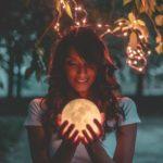 Vrouw met bruin haar een een wit shirt houdt een glazen bal vast welke prachtig licht geeft onder de bladeren van een verlichte boom