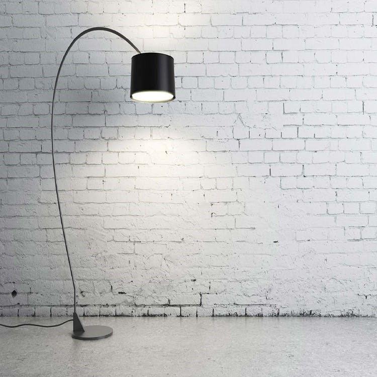 Minimalistische afbeelding met een witte stenen muur en een zwarte vloerlamp met grote steel
