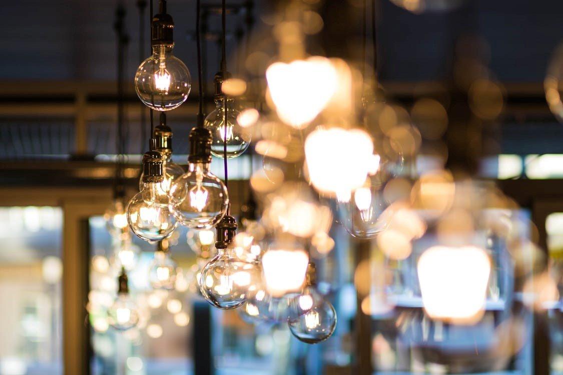 Veel gloeilampen die aan een plafond hangen in een kamer