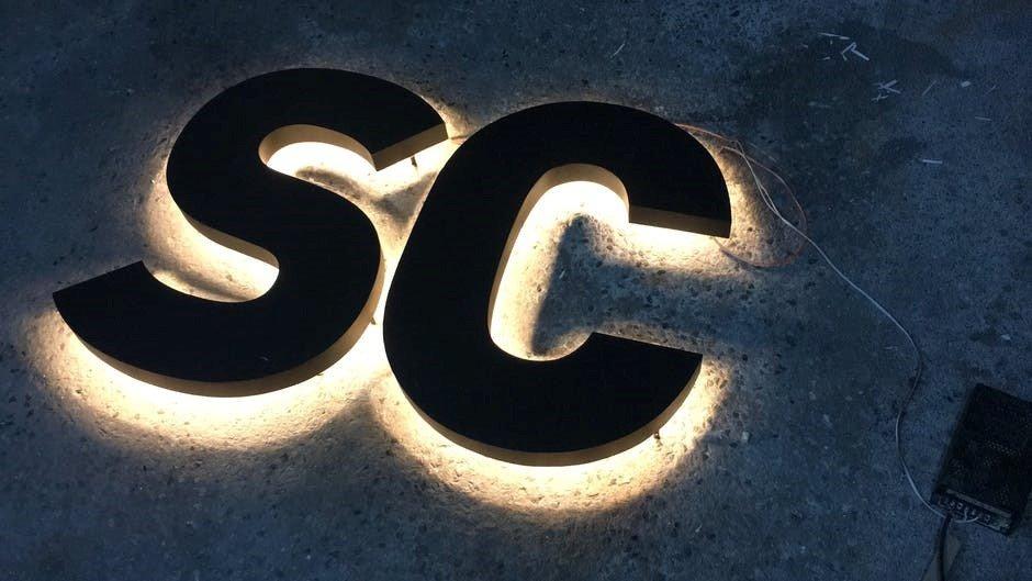 De twee letters SC zijn liggen op de grond waar er licht uit de onderkant komt