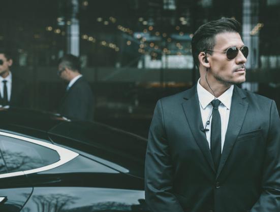 Een ingehuurde beveiliger in pak met zwarte zonnebril die voor een sportieve auto staat