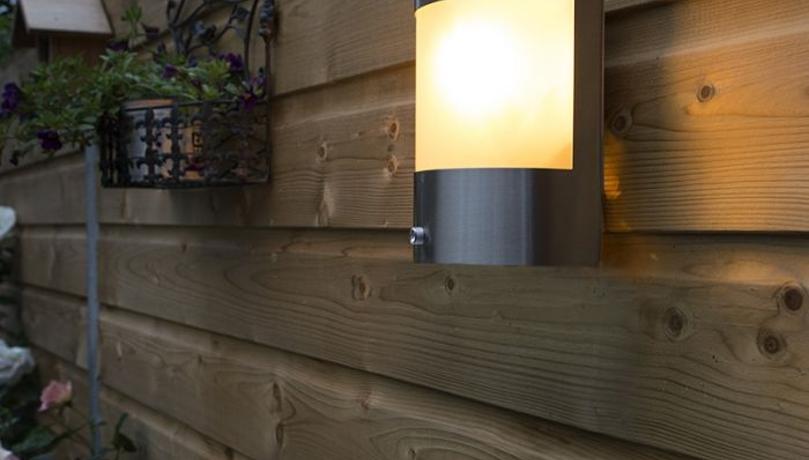 Sensorlamp die gevestigd is aan een bruin houten schutting