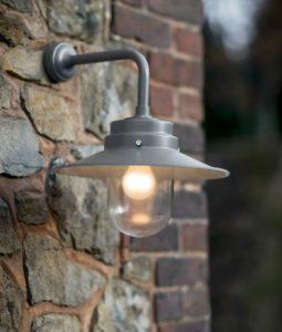 Zilveren lamp met grote kap die gevestigd is aan een stenen muur