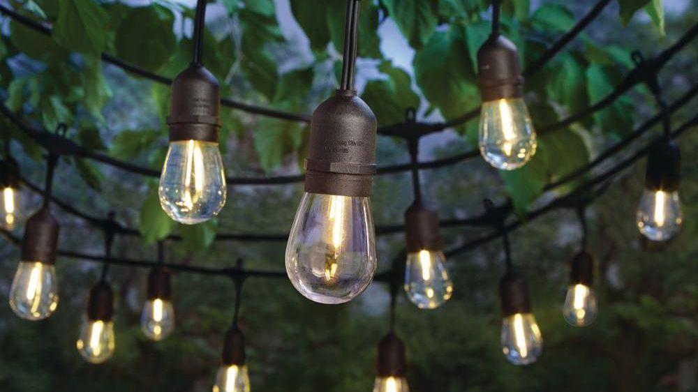 Gezellige zwarte string met lampen in een tuin